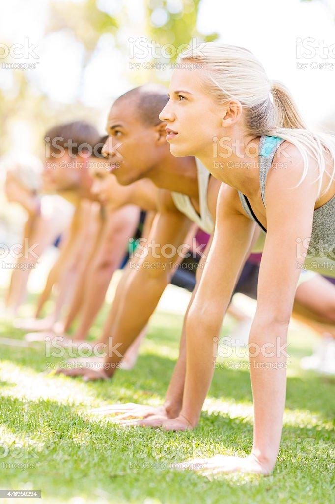 Woman With Friends Doing Push-Ups In Park stock photo