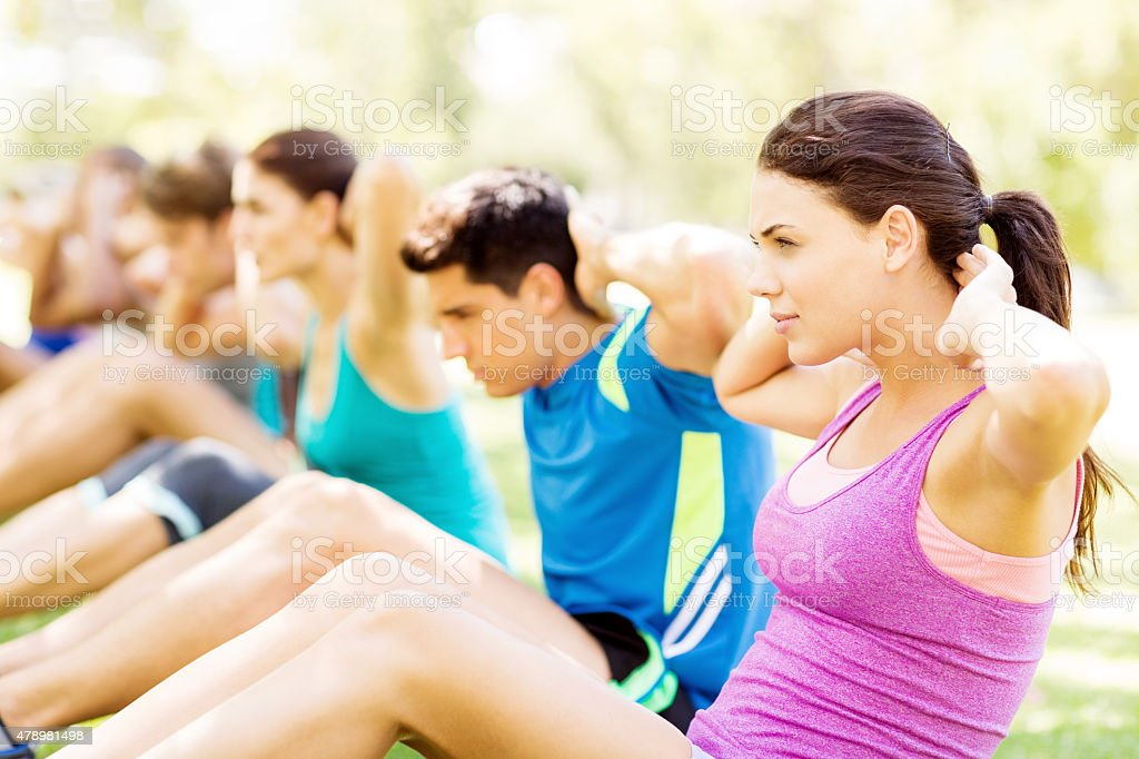 Woman With Friends Doing Sit-Ups In Park stock photo