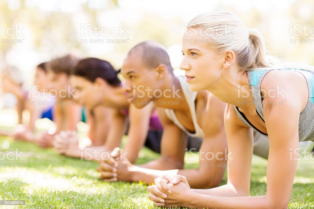 Woman With Friends In Plank Position In Bootcamp stock photo