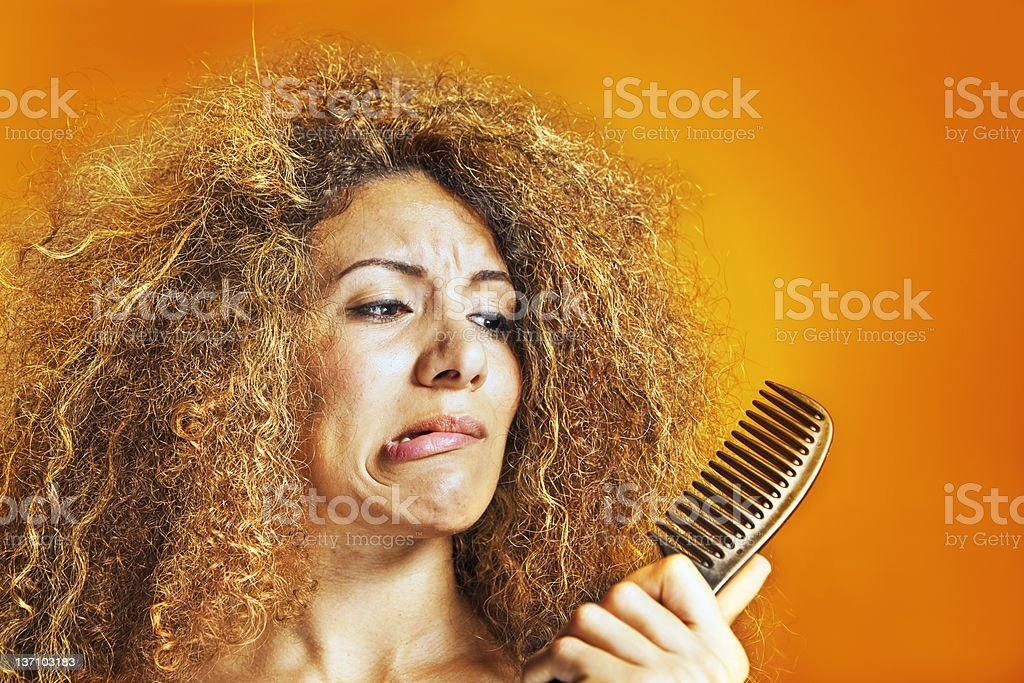 Woman with frizzy and curly hair looking at a comb stock photo