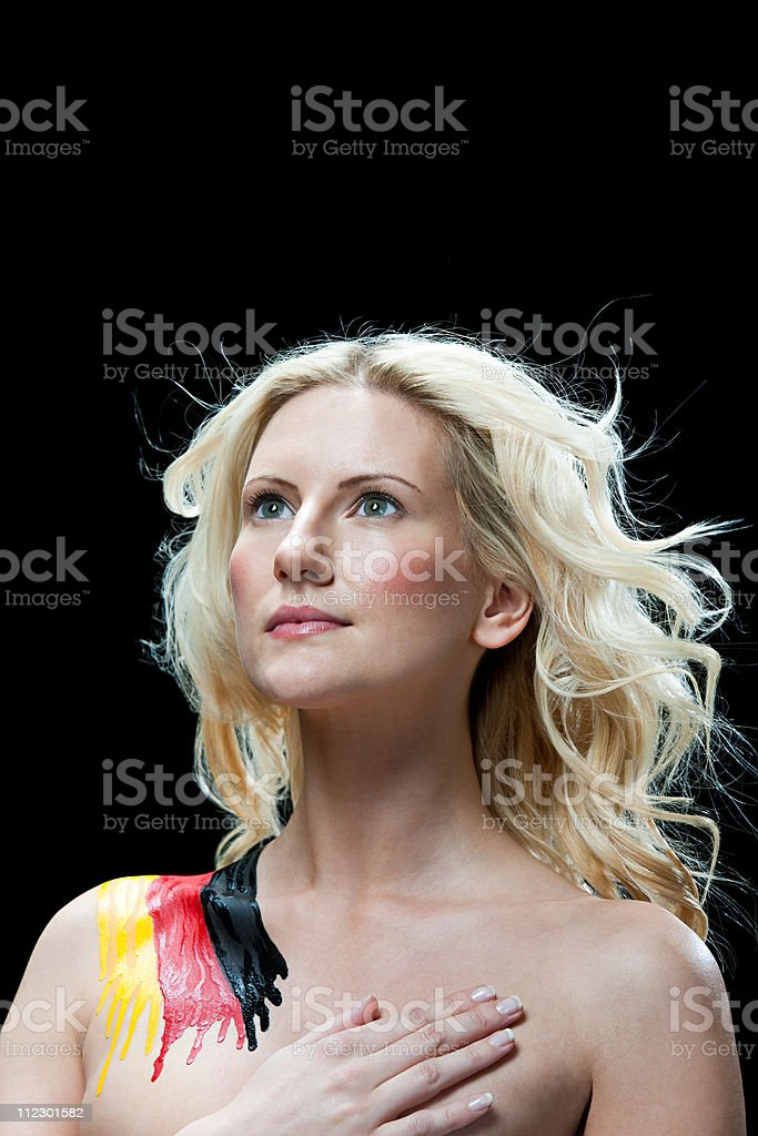 Woman with German flag painted on shoulder, hand on chest royalty-free stock photo