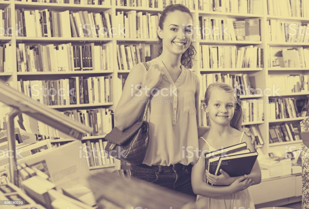 Woman with girl buying books stock photo
