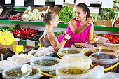 Woman with girl buying pickled olives