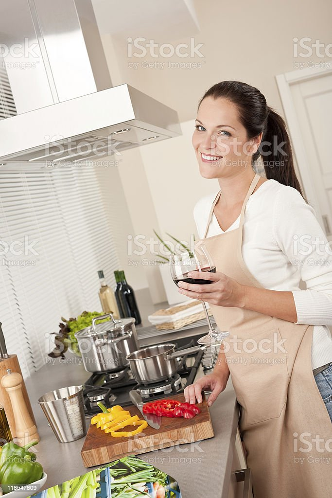 Woman with glass of red wine in the kitchen royalty-free stock photo