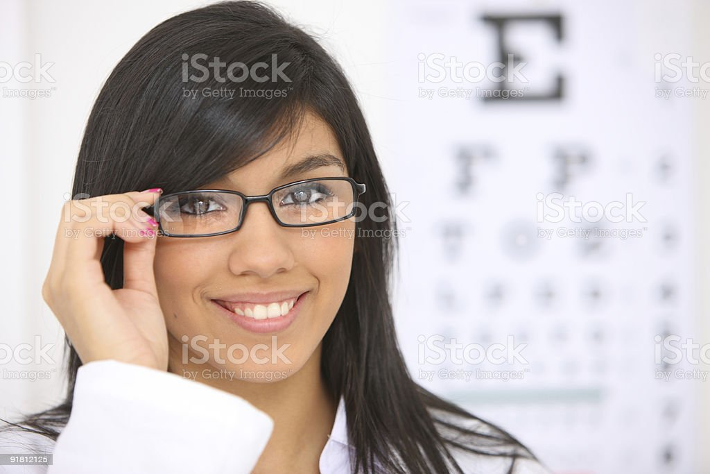 Woman with glasses, eye chart in background royalty-free stock photo