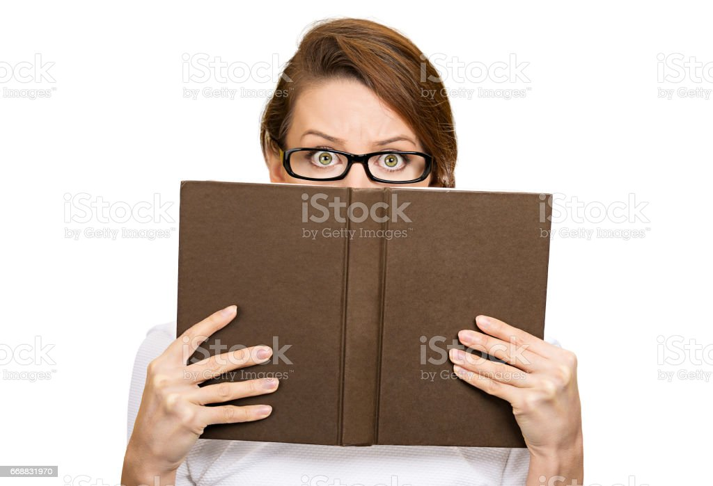 woman with glasses hiding her face behind book, stock photo