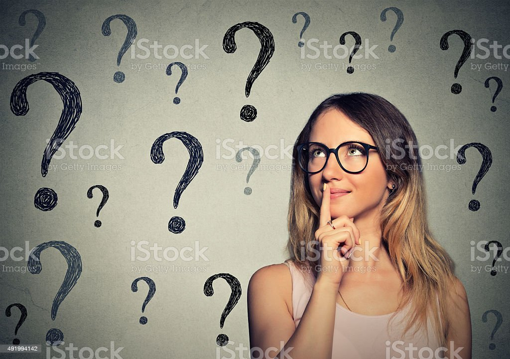 woman with glasses looking up at question marks stock photo
