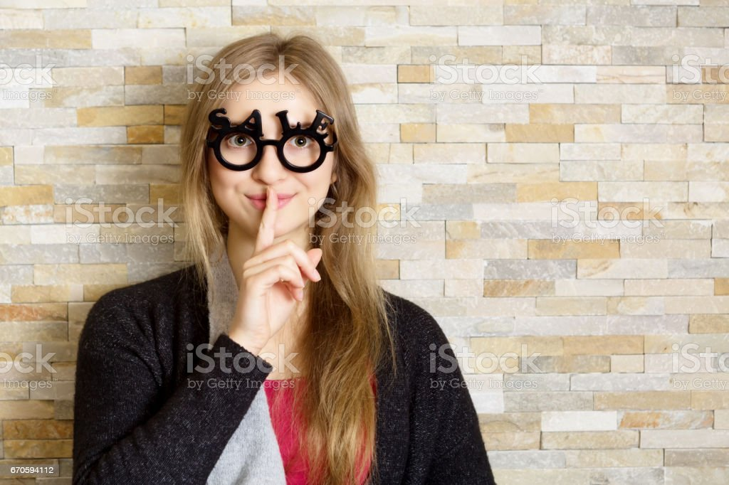woman with glasses shaped into SALE text stock photo