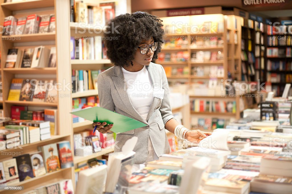 A woman with glasses working in a bookstore stock photo