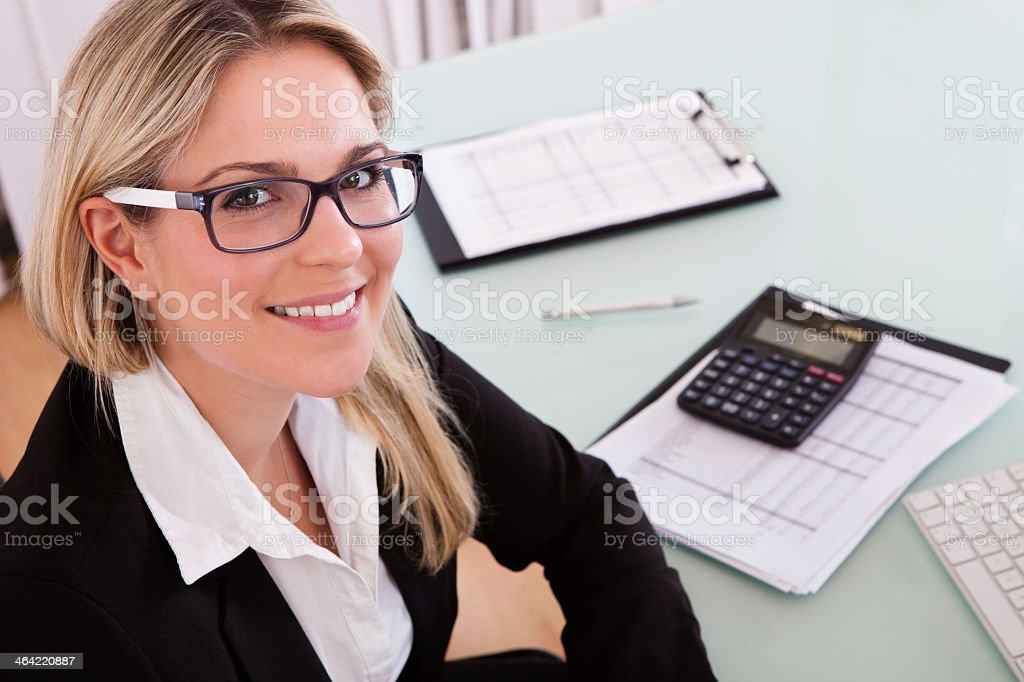 Woman with glasses working in an office with a calculator stock photo