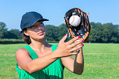 Woman with glove and cap catching baseball