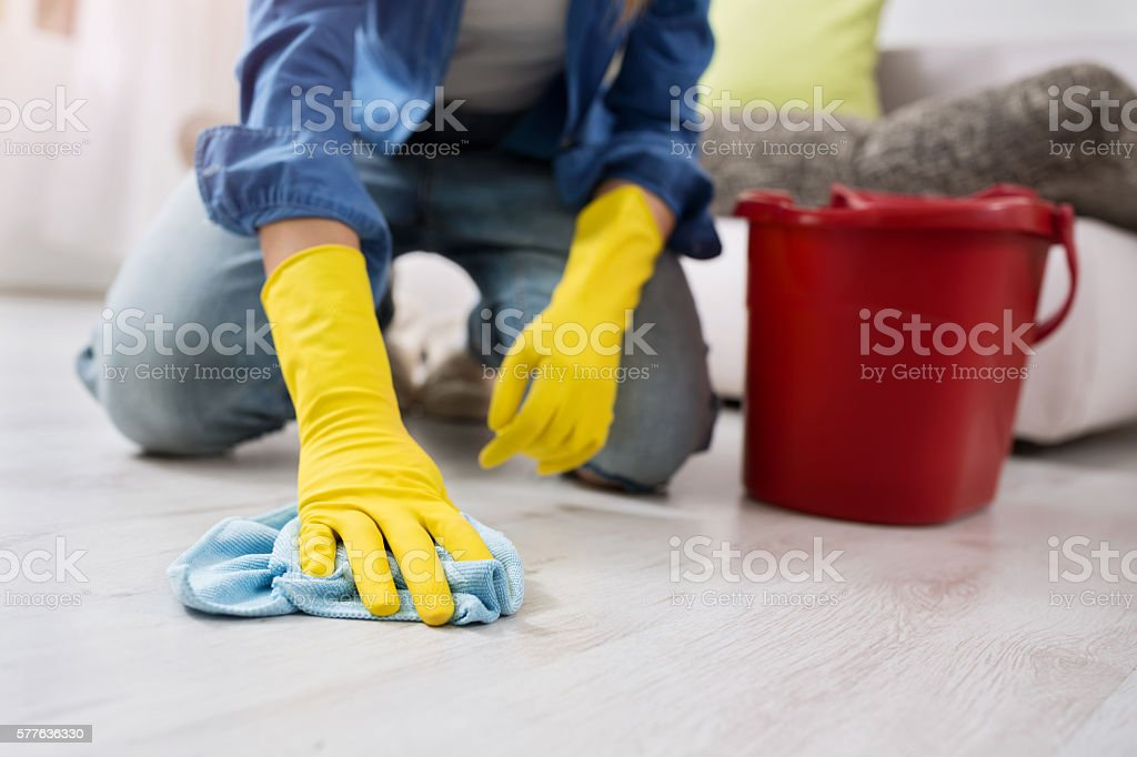 woman with gloves cleans the floor stock photo