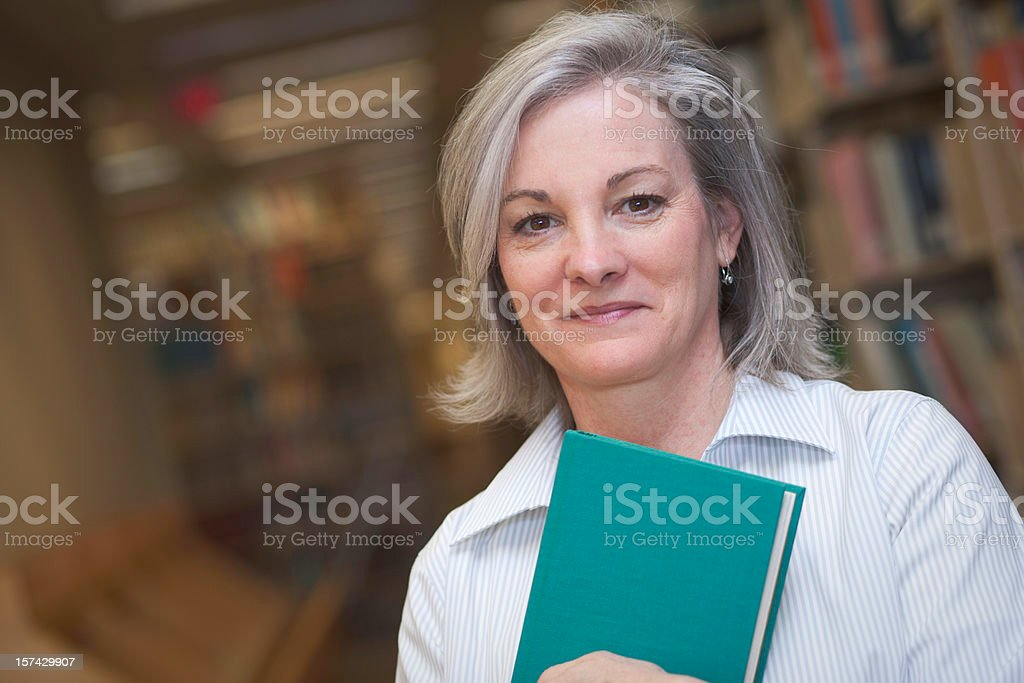 Woman with gray hair holding blue cover book in library royalty-free stock photo