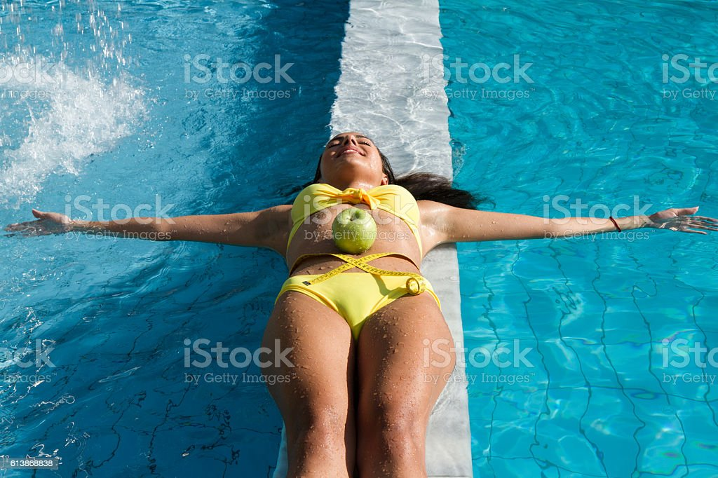 Woman with green apple and measuring tape on wet belly. stock photo