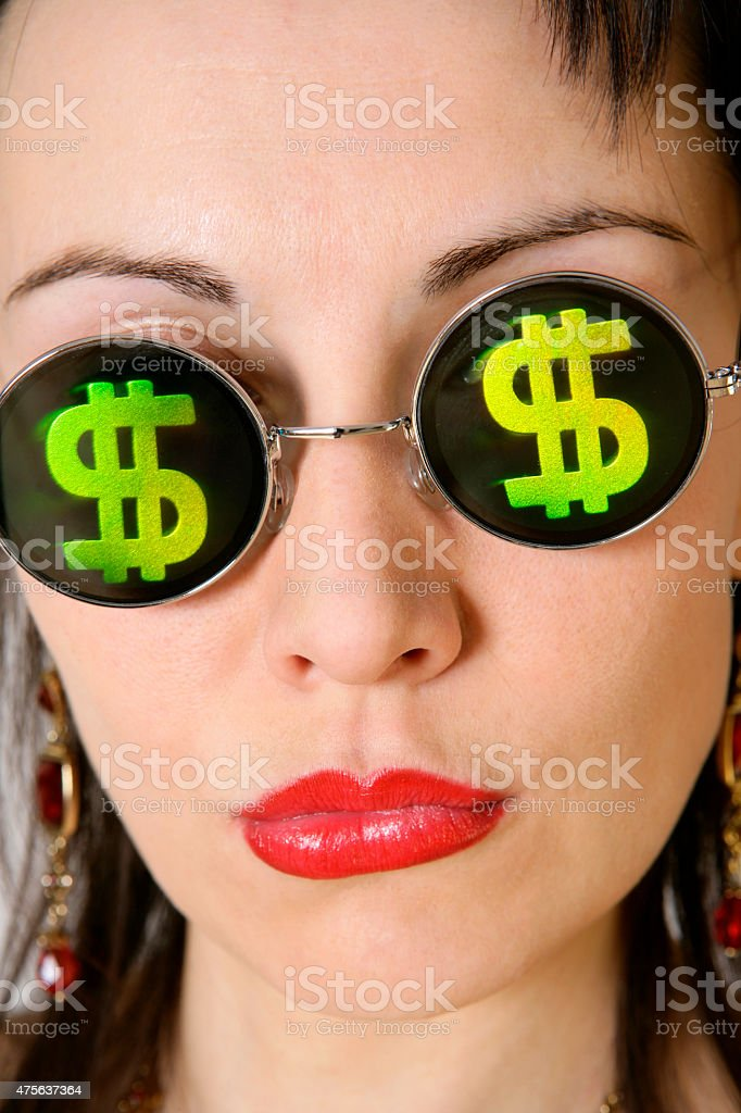 Woman with green dollar signs at her glasses stock photo