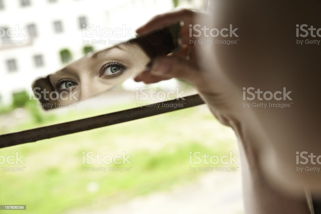Woman with Green Eyes Looking in Broken Piece of Mirror stock photo