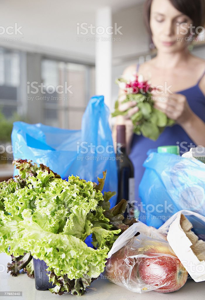Woman with groceries and flowers in kitchen stock photo