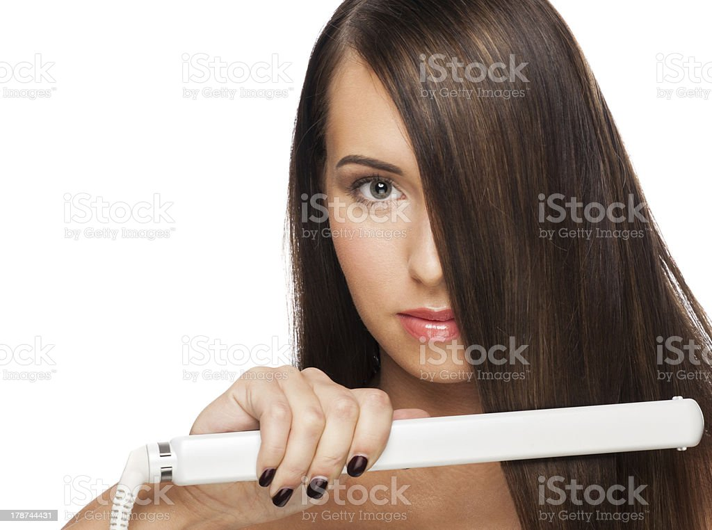 Woman with hair straightening irons stock photo