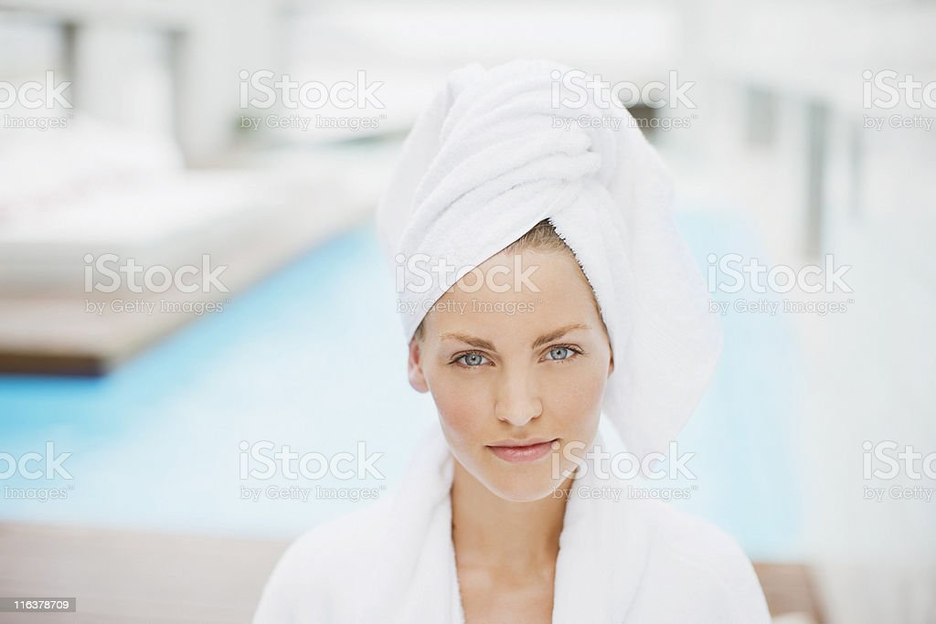 Woman with hair wrapped in towel at poolside stock photo