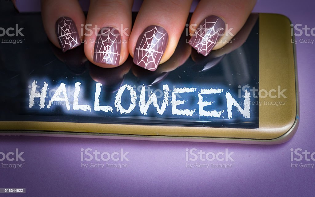 Woman with halloween cobweb nails on her glowing smartphone stock photo