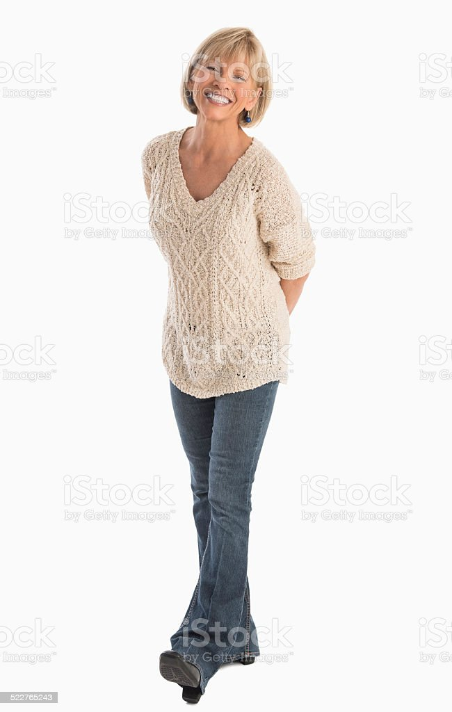 Woman With Hand Behind Back Walking Over White Background stock photo