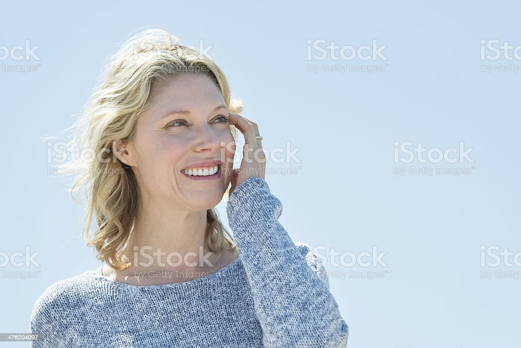 Woman With Hand In Hair Looking Away Against Clear Sky stock photo