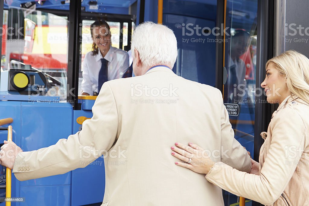 Woman with hand on senior man's back helping him board a bus stock photo