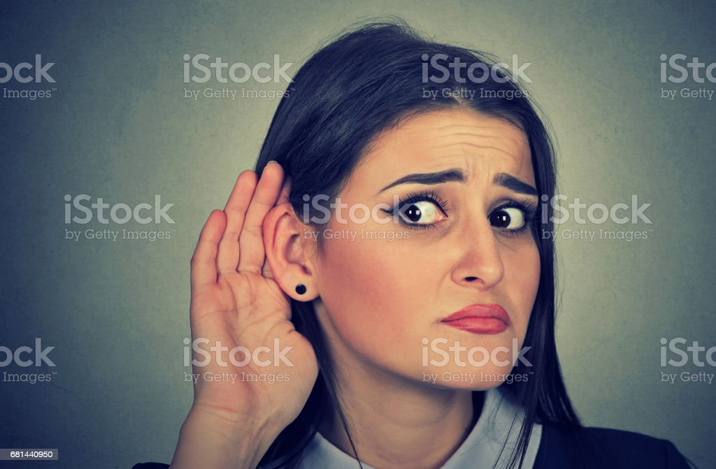 Woman with hand to ear gesture listening carefully stock photo