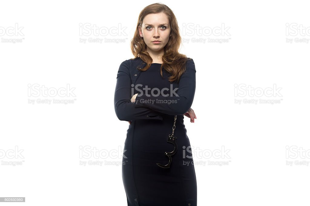 Woman with handcuffsand arms crossed stock photo