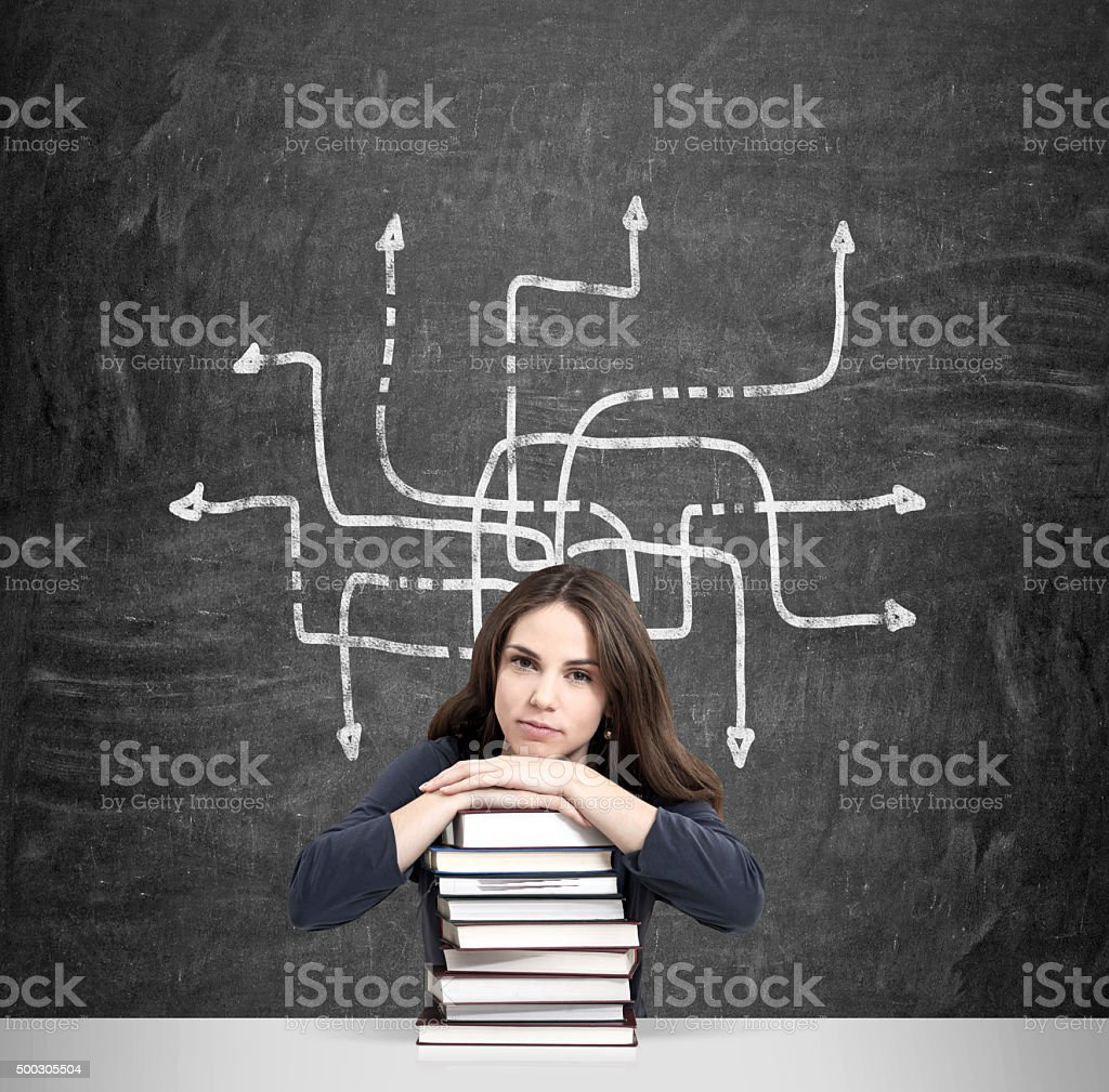 woman with hands and head on pile of books thinking stock photo