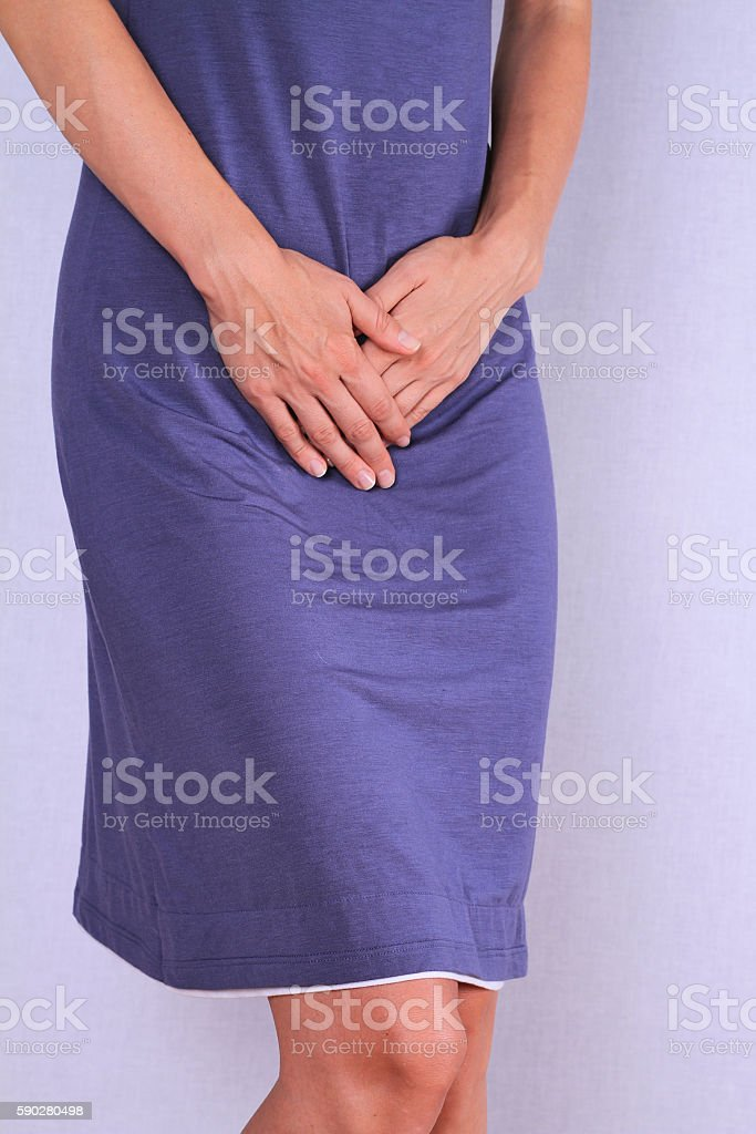 Woman with hands holding her crotch close up. stock photo