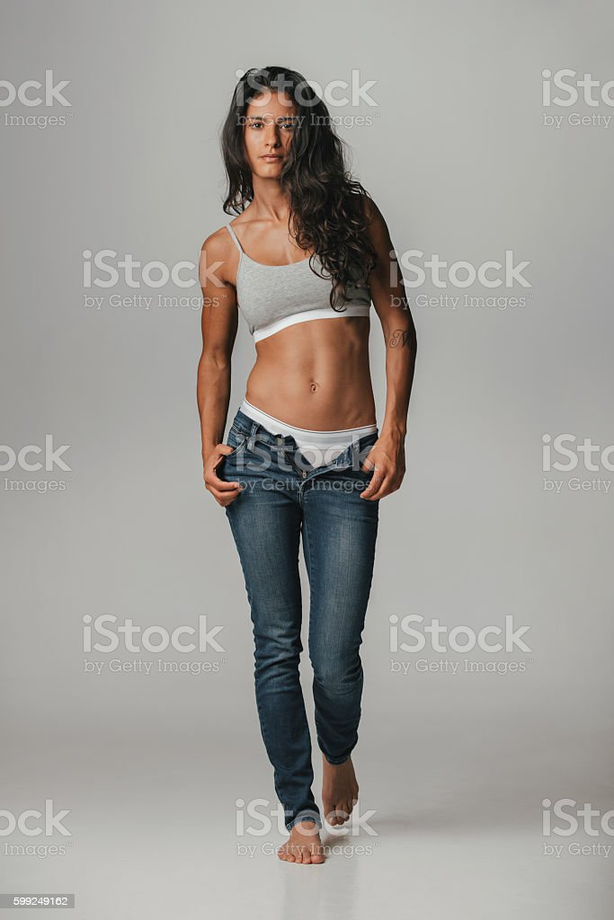 Woman with hands in pockets of unzipped pants stock photo