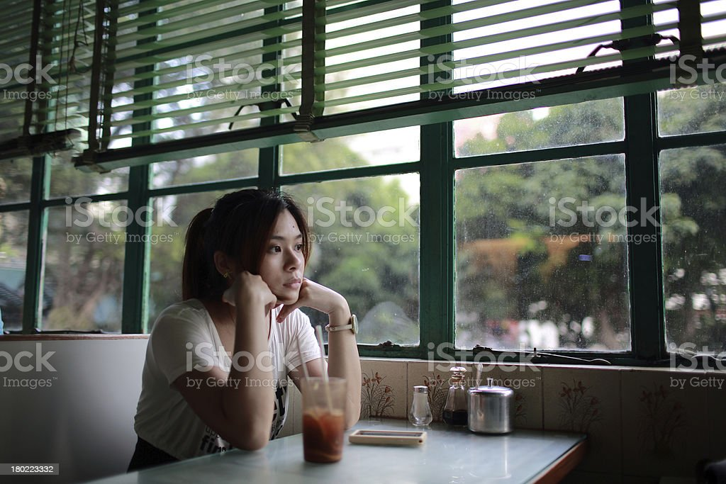 Woman with hands on chin at restaurant table stock photo
