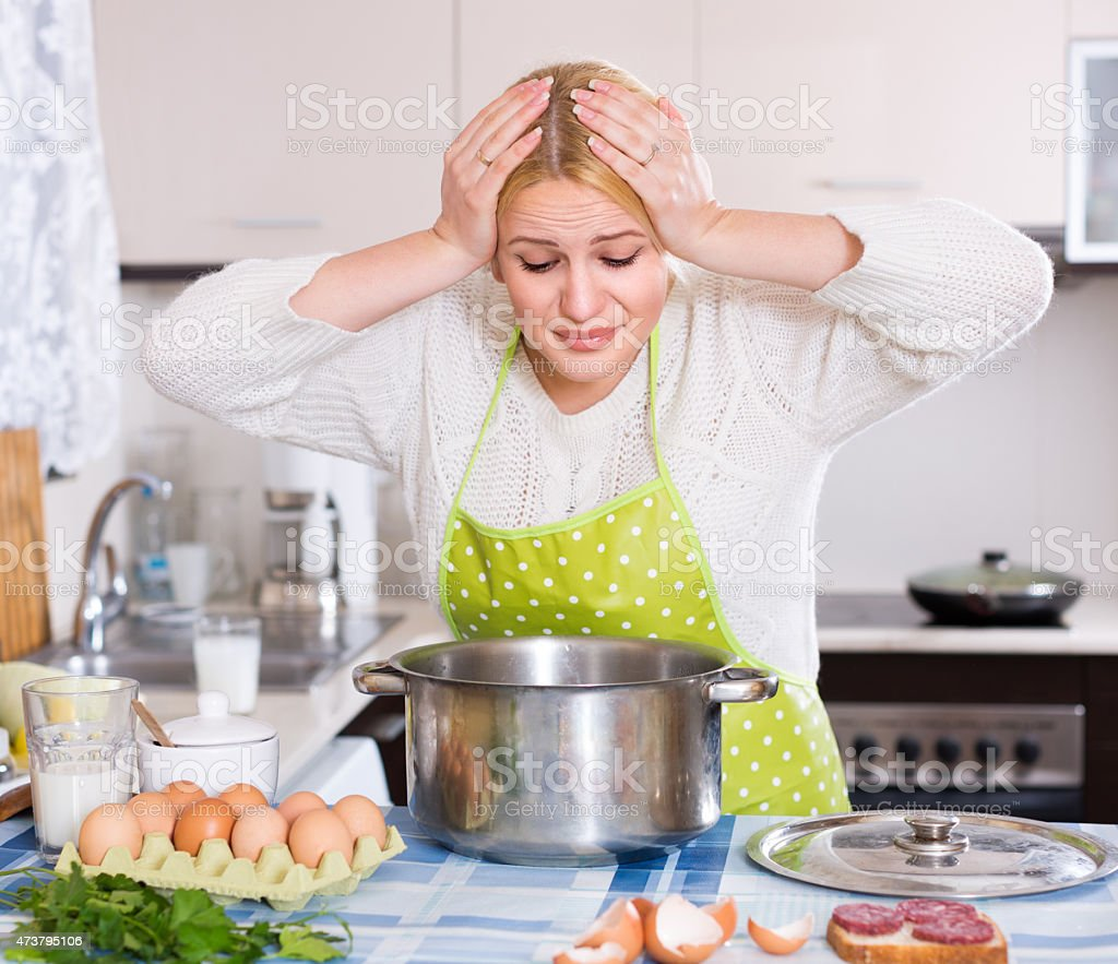 Woman with  hands on head smelling bad odors from pan stock photo