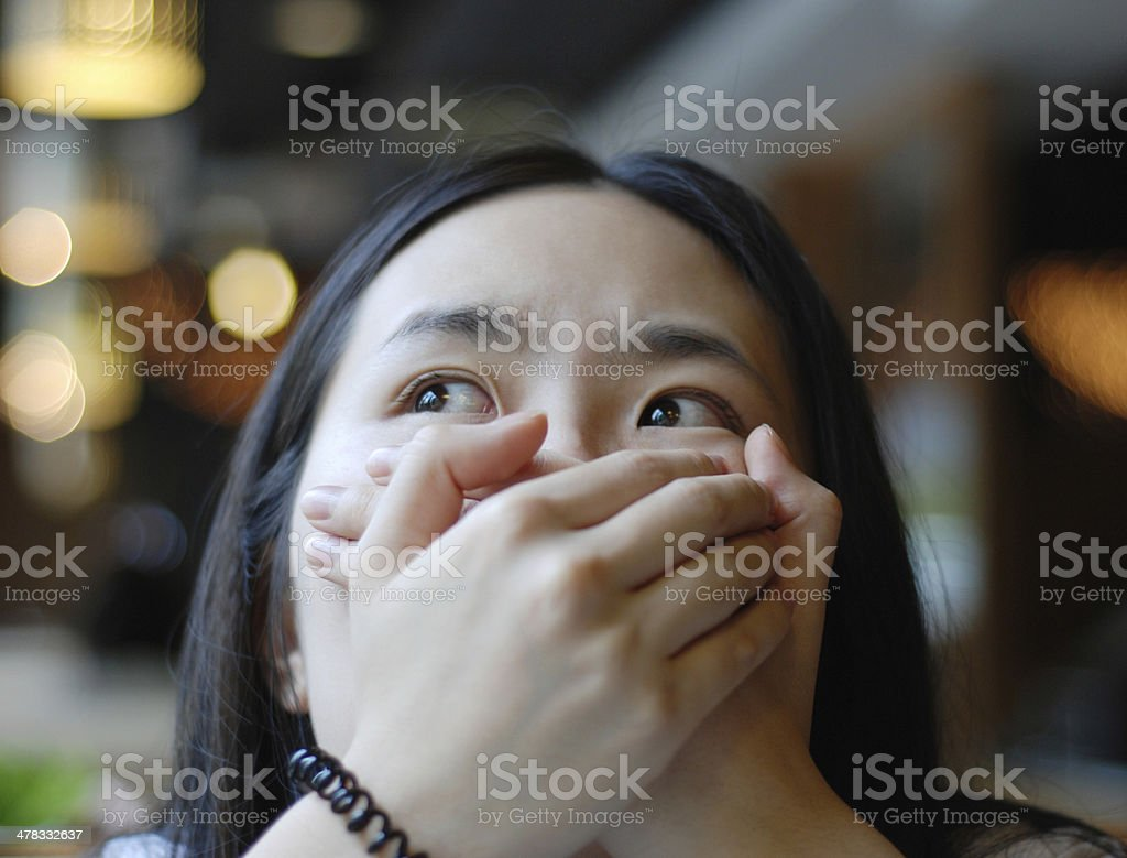 woman with hands on mouth stock photo