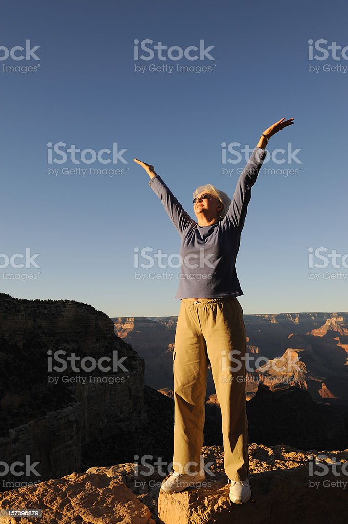 Woman with Hands Raised at Edge of the Grand Canyon royalty-free stock photo