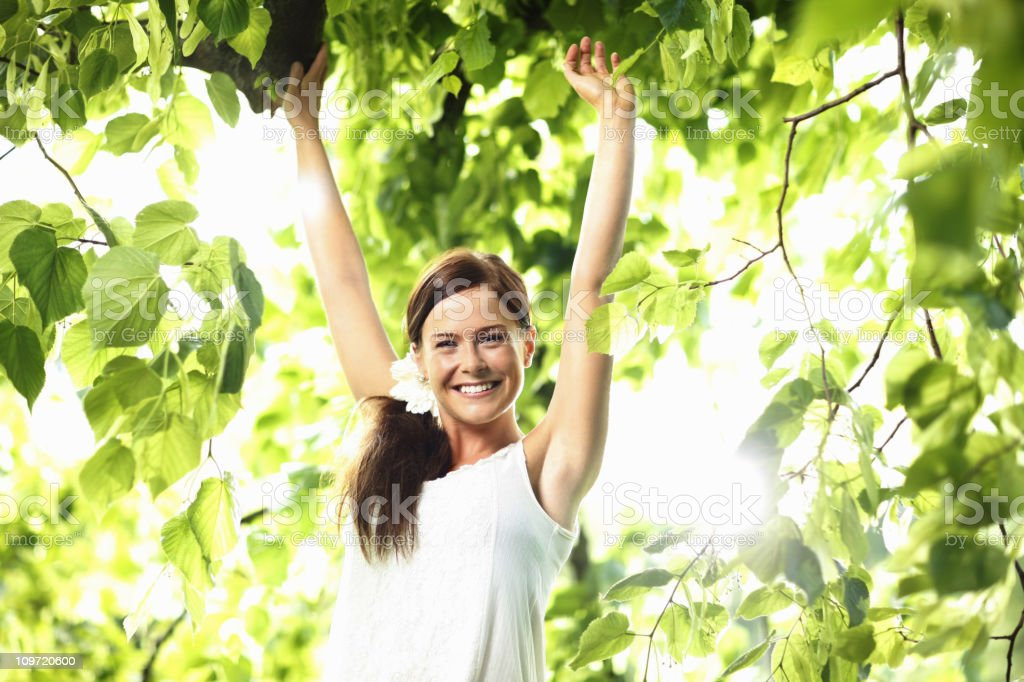 Woman with hands raised enjoying fresh air in green forest royalty-free stock photo
