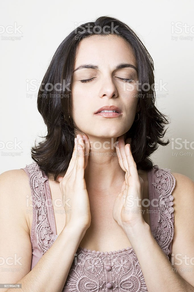 Woman with hands to her throat looking pained stock photo