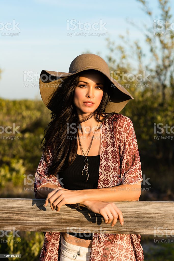 Woman with hat standing in field stock photo