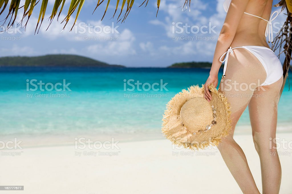 woman with hat under palm tree at the Caribbean beach royalty-free stock photo