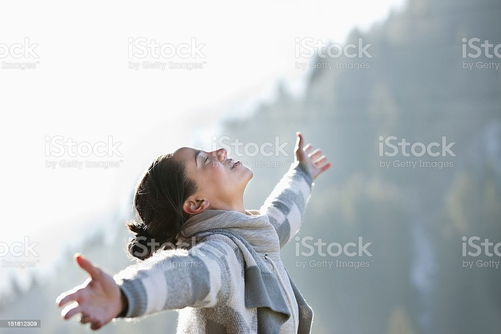 Woman with head back and arms outstretched stock photo