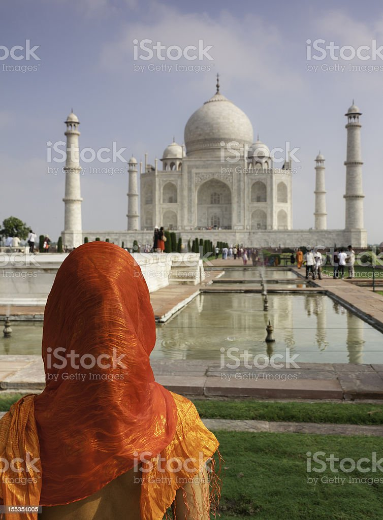 Woman with head covered looking at Taj Mahal stock photo