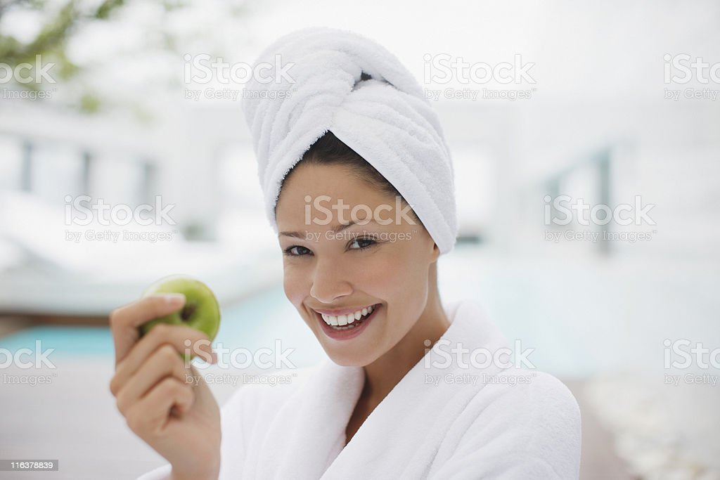 Woman with head wrapped in towel eating apple at poolside stock photo