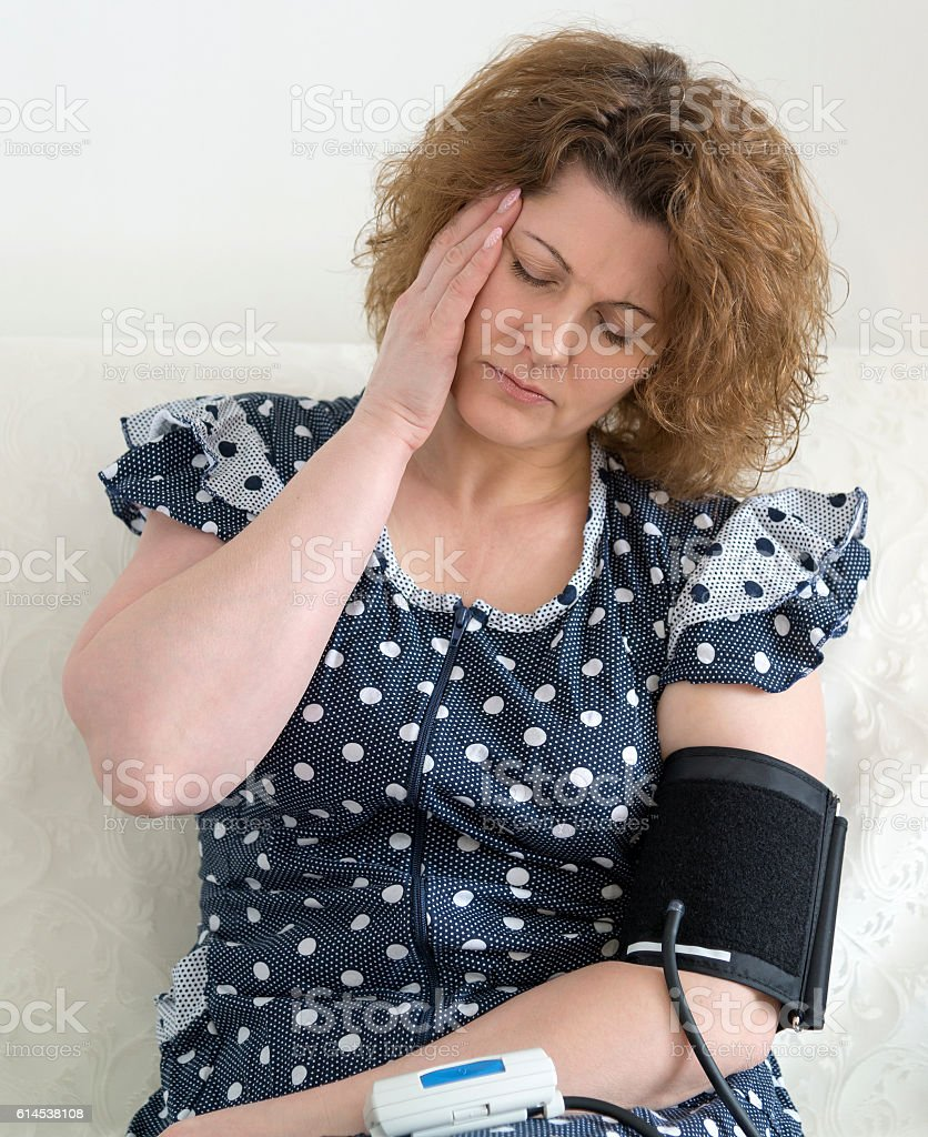 Woman with headache measures blood pressure stock photo
