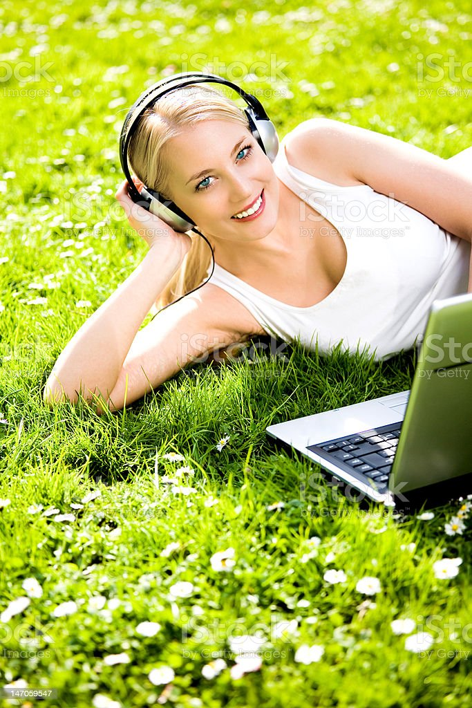 Woman with headphones and laptop outdoors royalty-free stock photo