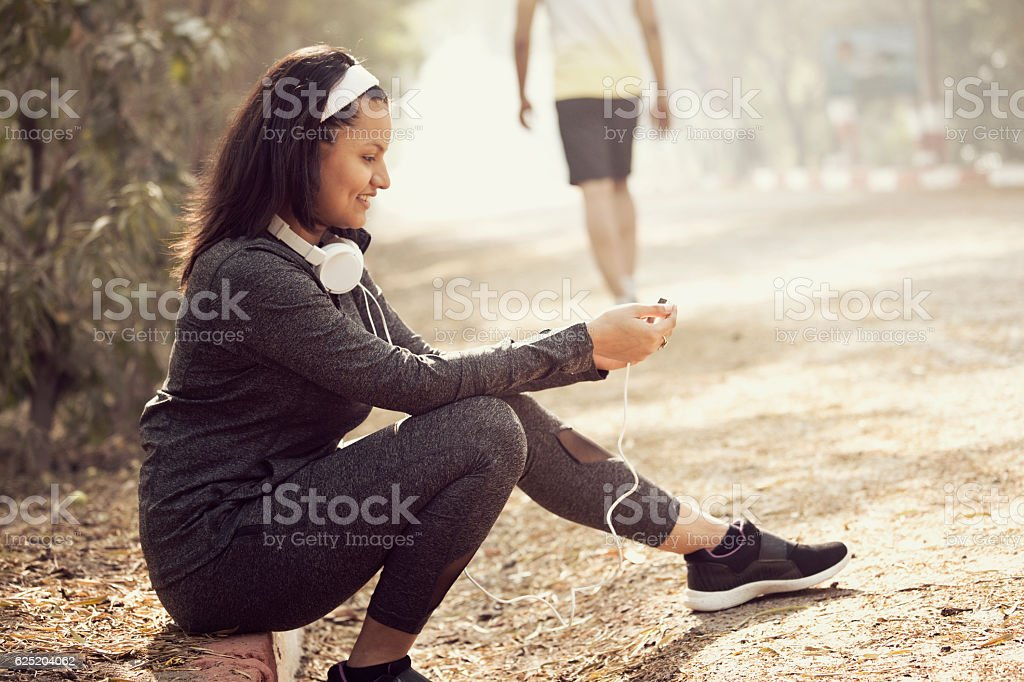 Woman with headphones and smart phone at park stock photo