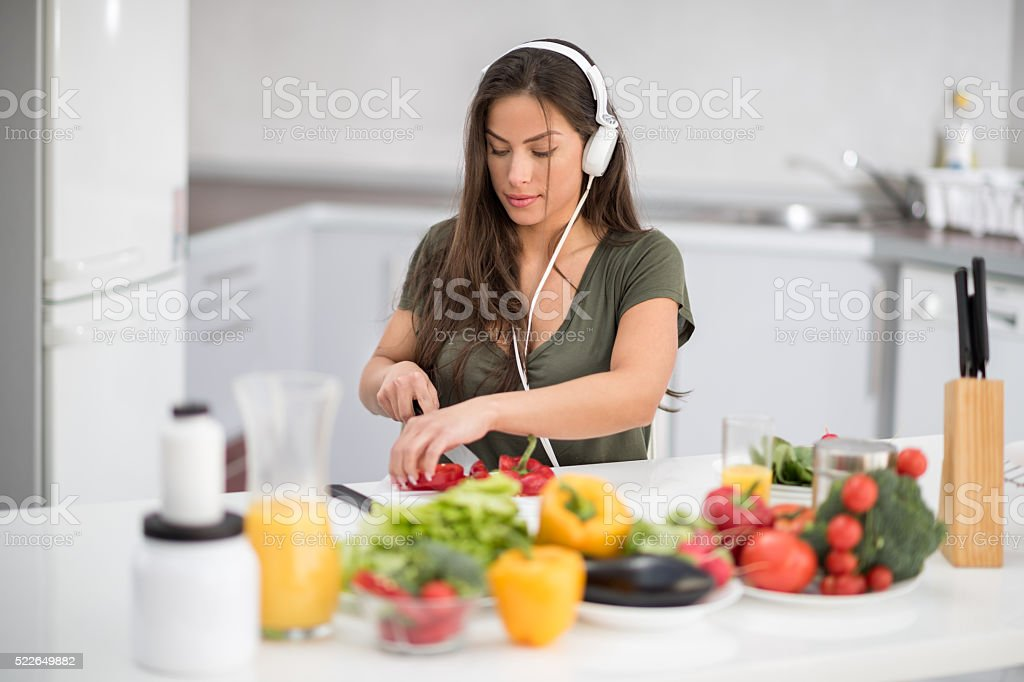 Woman with headphones cutting bell pepper stock photo