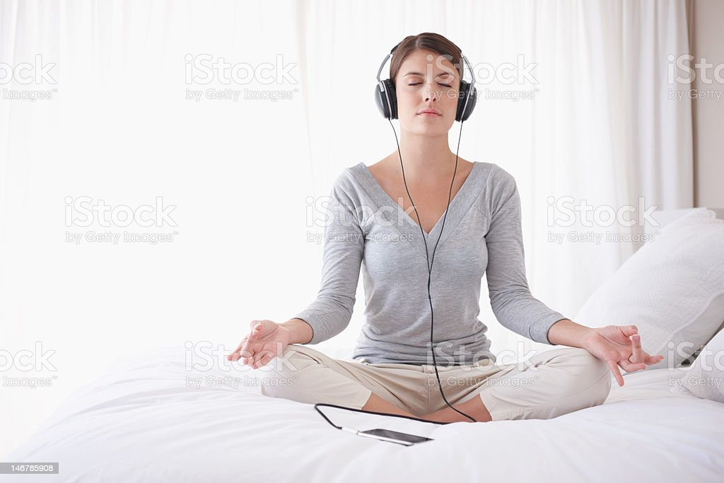 Woman with headphones in lotus position on bed stock photo