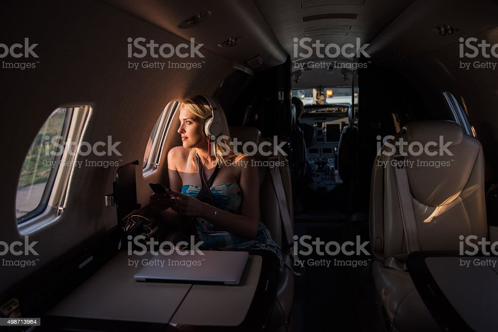 Woman with headphones inside private jet airplane stock photo