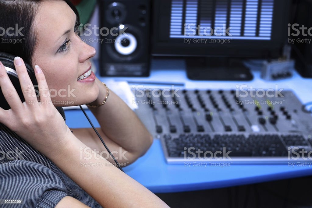 Woman with headphones on listening to a live recording stock photo